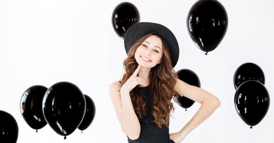 Una mujer viendo la ´cámara con globos negros de fondo.