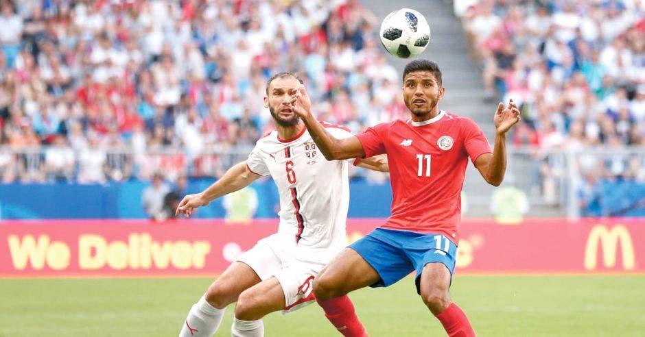 Johan Venegas disputa un balón frente a un jugador de Serbia, en el Mundial