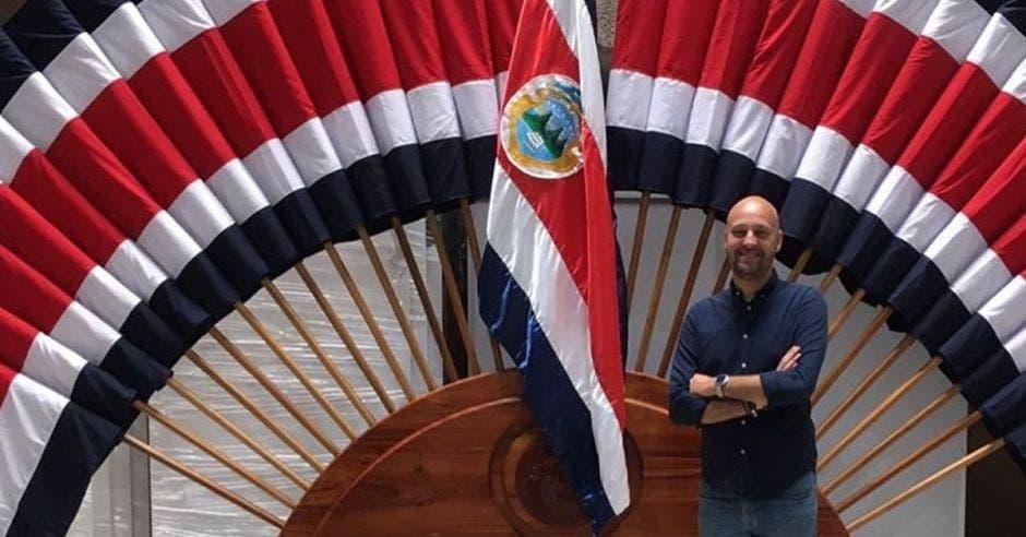 Federico Cartín posa frente a un pabellón nacional. En el fondo se ven un montón de banderas.