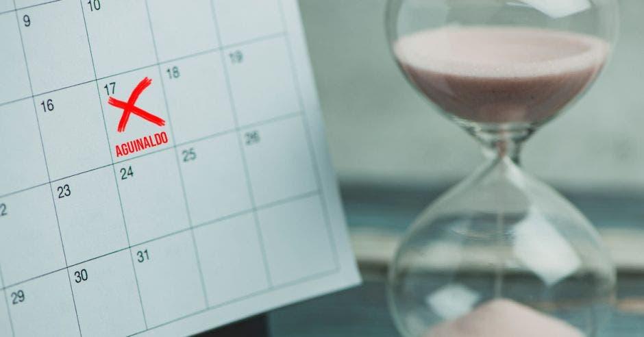 Un calendario con una equis y la palabra aguinaldo al lado de un reloj de arena
