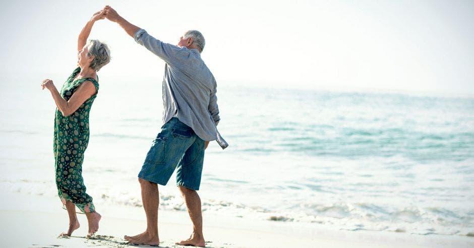 Una pareja de adultos mayores baila en la playa