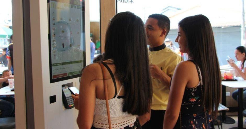 Un dependiente explica a dos mujeres el uso de las pantallas táctiles de autoservicio