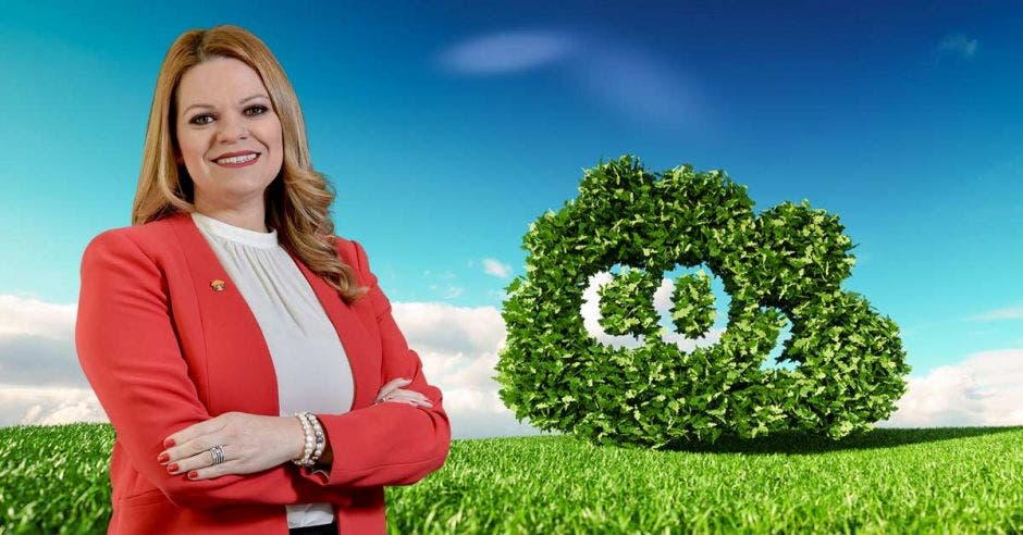 Leticia arguedas posa con un blaser rojo junto a una nube verde hecha de arbustos