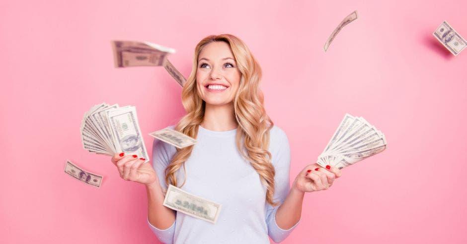 Mujer feliz por contar con muchos billetes en su mano
