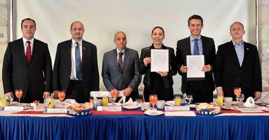 Seis personas frente una mesa d etrabajo, dos de las cuales sostienen el convenio firmado en sus manos.