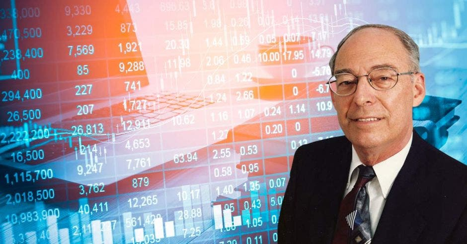 fondo de computadora con números y gráficos,  Eduardo  Lizano en primer plano al  lado derecho.