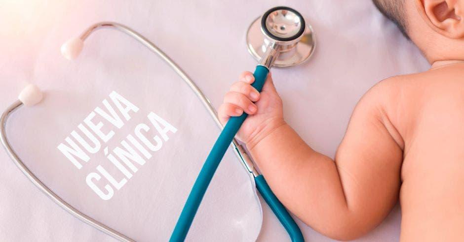 Un bebé agarrando un estetoscopio y la palabra nueva clínica