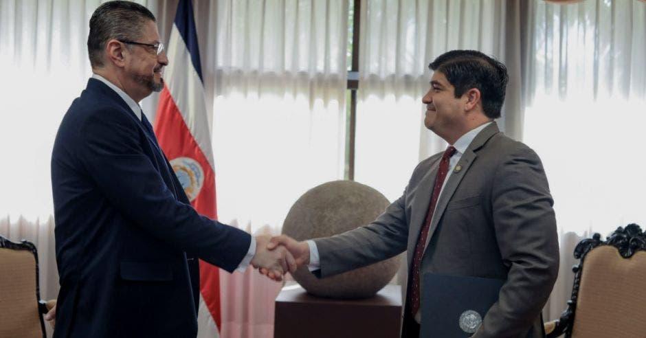 Carlos alvarado le da la mano al nuevo ministro de hacienda.