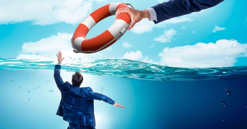 Una mano aparece con un salvavidas y se lo ofrece a una persona que se encuentra hundida en el mar, con solo una mano fuera de él