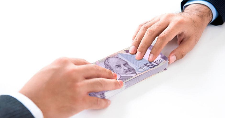 fondo blanco, dos manos pasándose un fajo de billetes de cincuenta mil colones