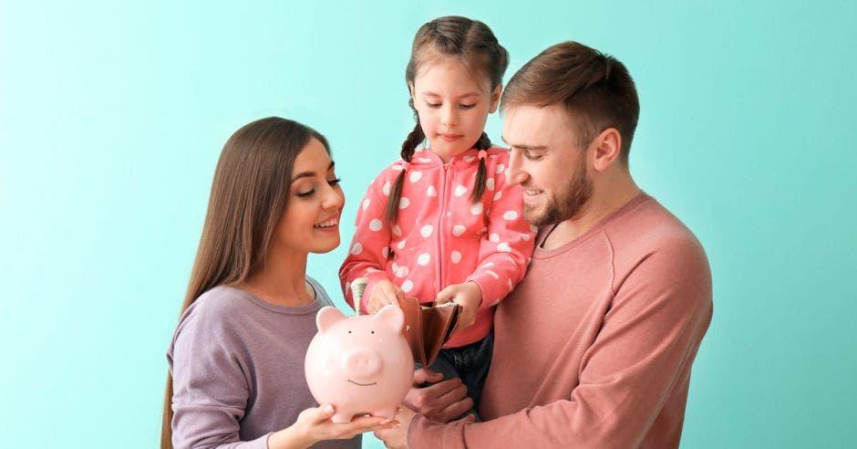familia de tres personas, una mujer, y un hombre alzando a una niña, sostienen una alcancía de chancho rosada