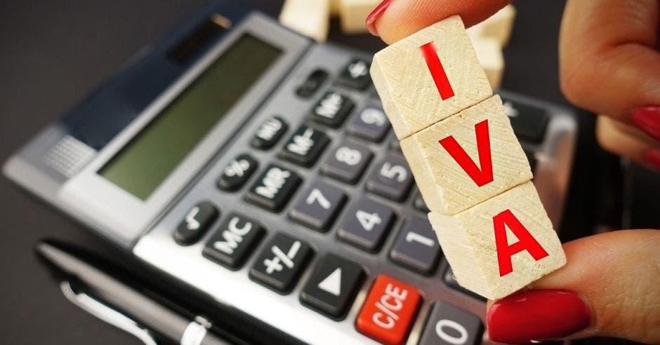Mano sosteniendo cuadrados con el nombre IVA mientras saca cálculos en su calculadora