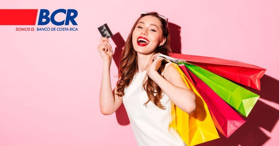 fondo rosado con mujer con bolsas de colores a la espalda agarradas de una mano, y en la otra una tarjeta de crédito negra. Logo del BCR en el superior izquierdo