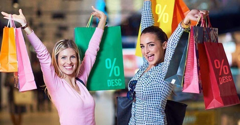 Mujeres celebrando sus compras levantando sus bolsas de productos en descuento