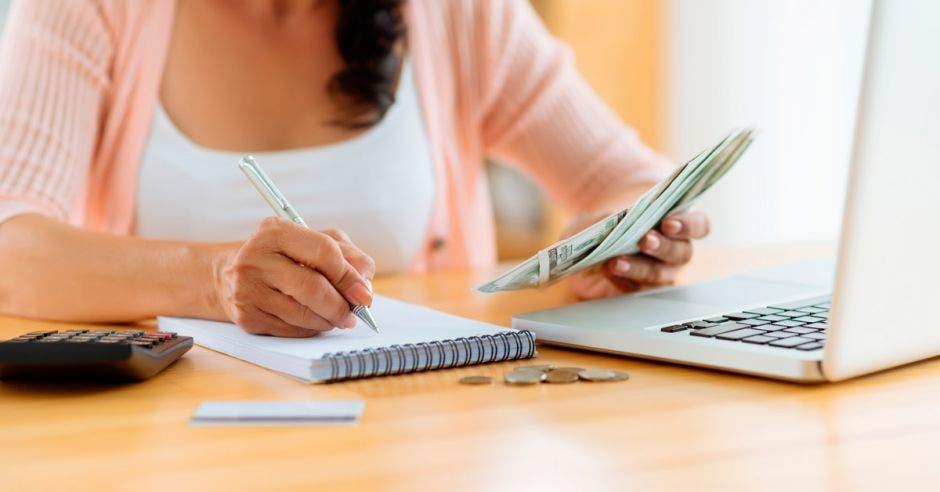 mujer realiza cálculos de su presupuesto con su computadora, libreta y calculadora. En la mano derecha sostiene dinero.