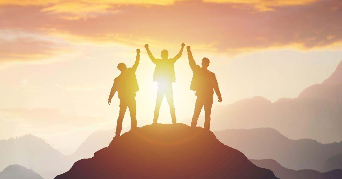 Tres amigos celebran en la cima de una montaña