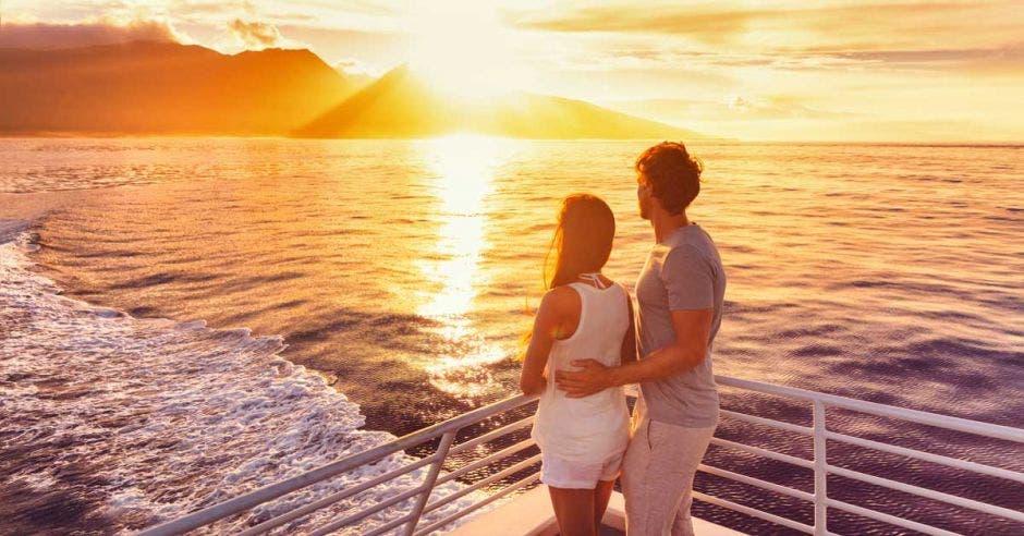 Una pareja disfruta de la puesta de sol a bordo de un crucero