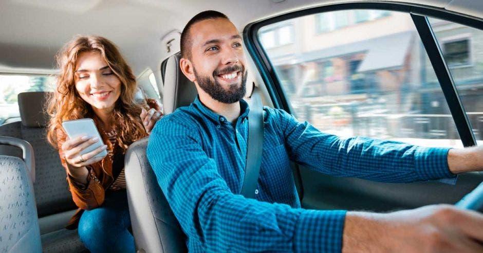Un conductor de Uber sonríe y la pasajera del asiento de atrás también sonríe