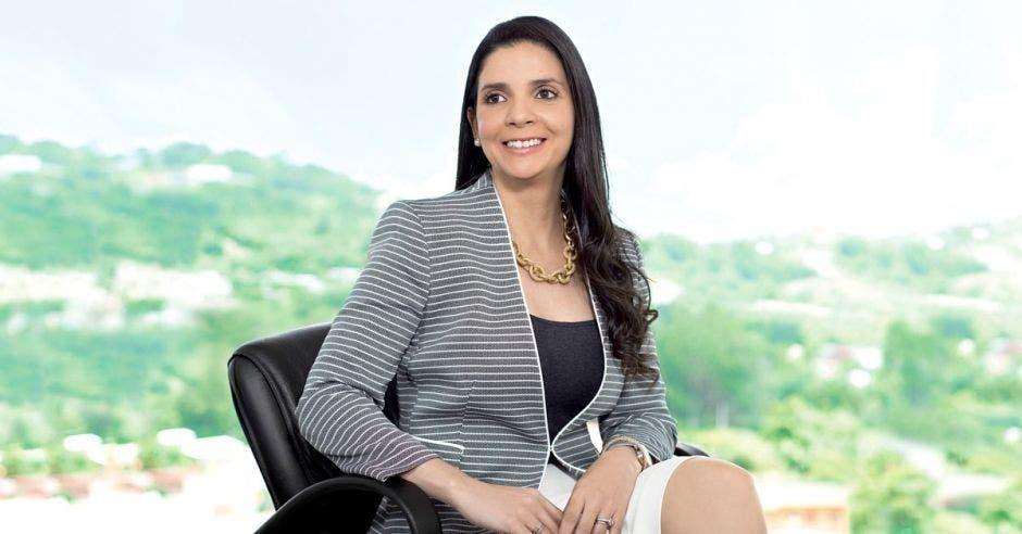 Andrea Centeno, presidenta ejecutiva de Japdeva, sentada en una oficina con las instalaciones portuarias de fondo.
