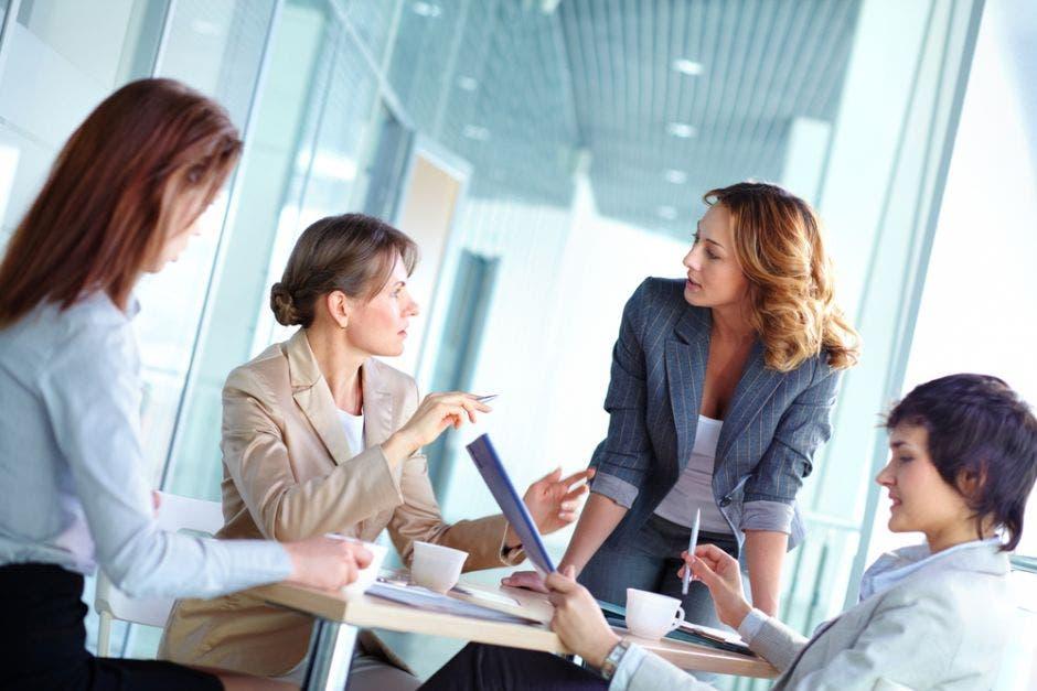 grupo de cuatro mujeres  unidas trabajando en una oficina
