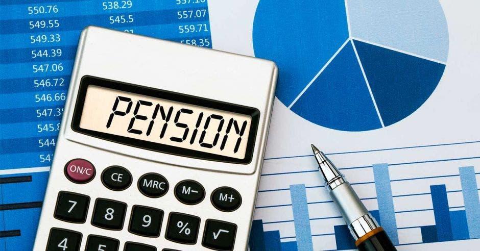 calculadora con la palabra pensión, gráficos azules y lapicero al lado de la calculadora