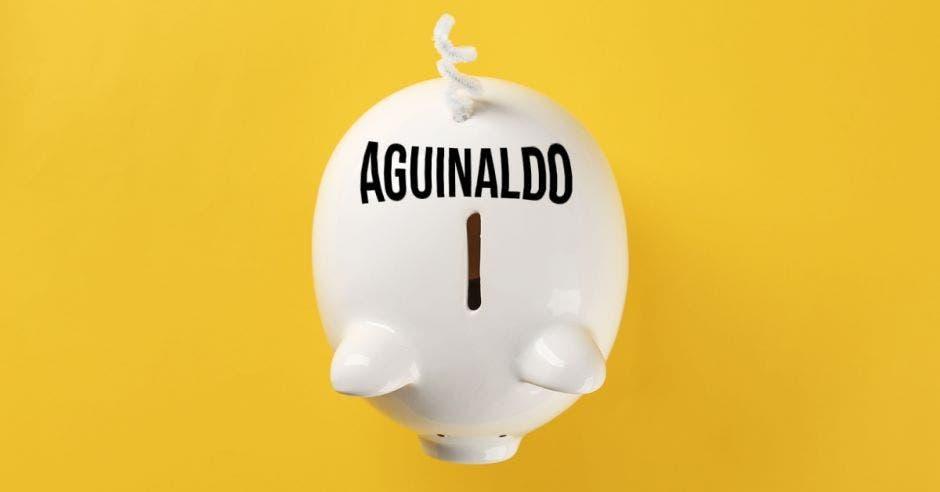 fondo amarillo con un chanchito de alcancía visto desde arriba con la palabra aguinaldo en la parte de atrás de su espalda