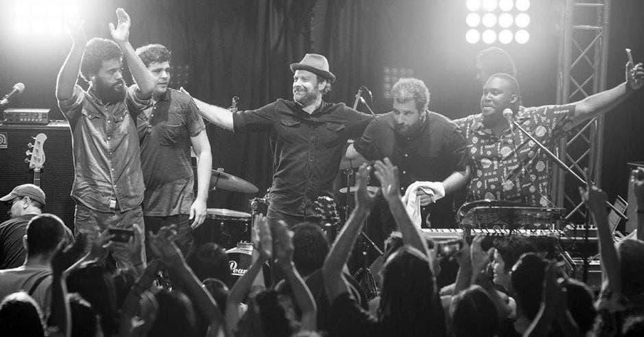 Varios de los integrantes de Señor Loop en una tarima al terminar uno de sus conciertos, una foto blanco y negro