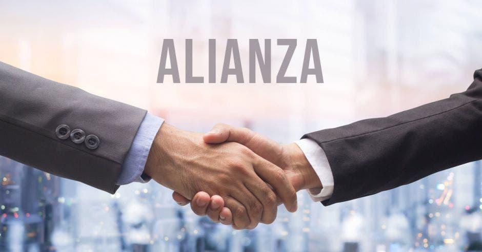 dos personas se dan la mano en señal  de trato  con la palabra alianza encima