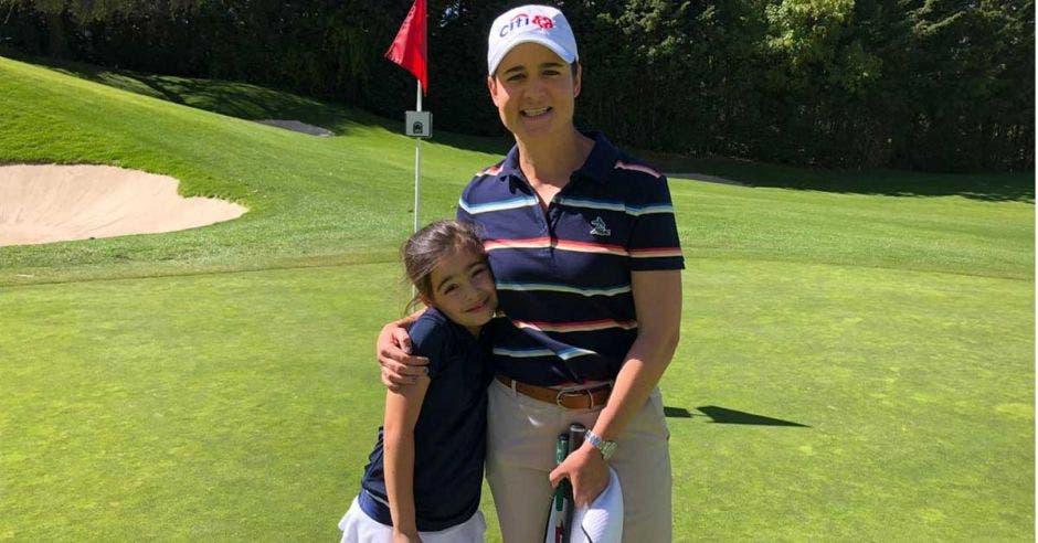 niña y mujer posan en golf