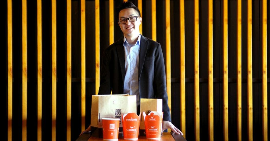 Owen Chen posa junto a varios tarros de comida de Canton color naranja