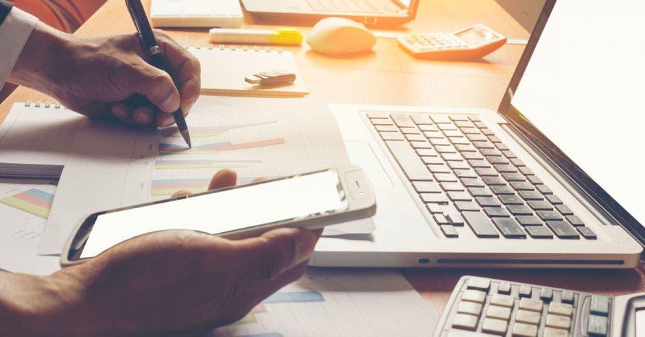 persona realizando cálculos con una computadora, calculadora y celular