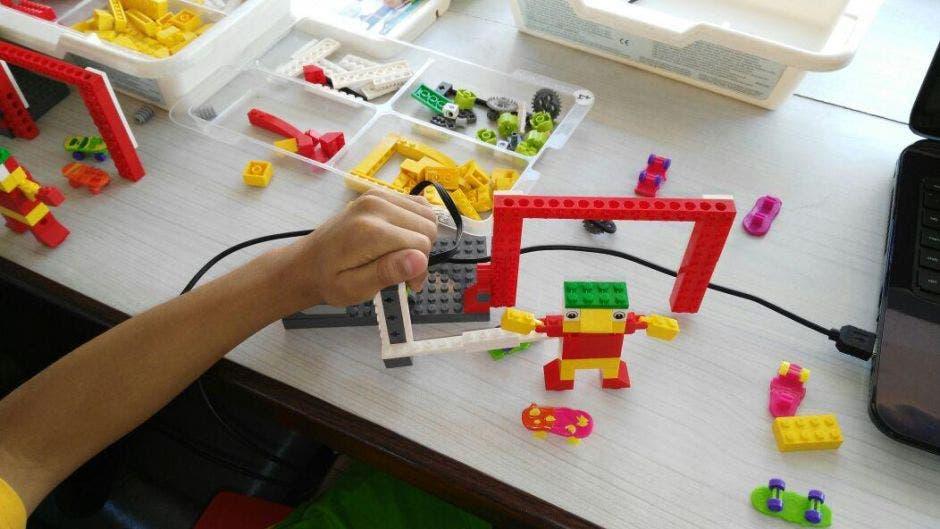 La mano de una niña jugando con legos.