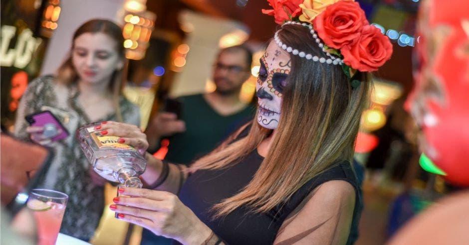 Mujer pintada de Catrina sirviendo tequila