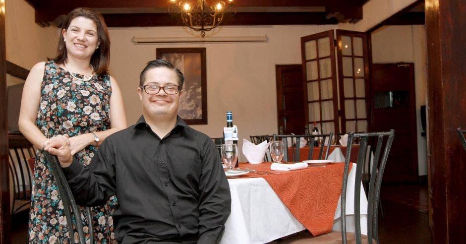 La gerente del restaurante junto a su hijo con síndrome de down, sonrientes, en el restaurante