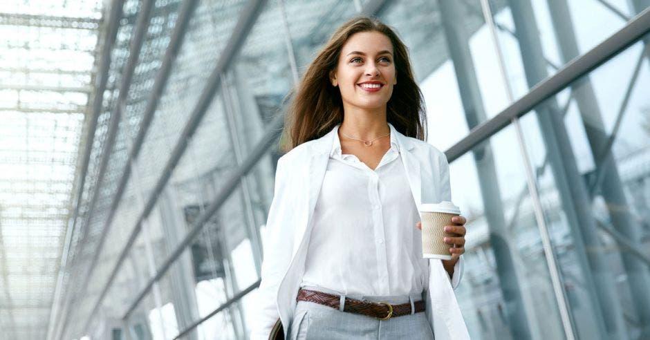 Una mujer con blusa blanca y pantalón gris camina en frente de un vitral