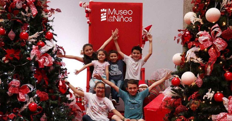 Varios niños alzando las manos en este sector navideño del Museo de los niños, con dos árboles a los lados