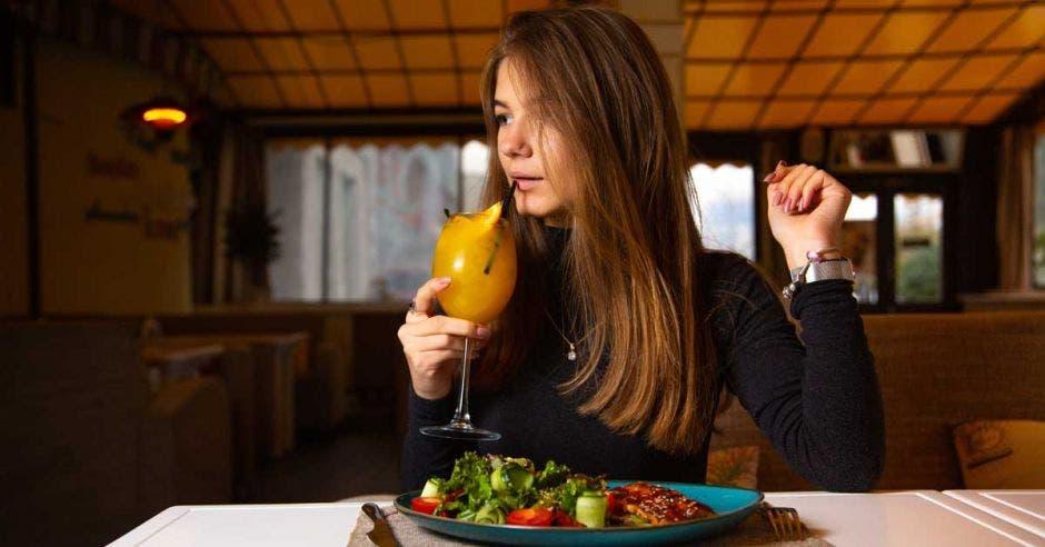 Una mujer disfruta de una mimosa y un platillo de carne con ensalada
