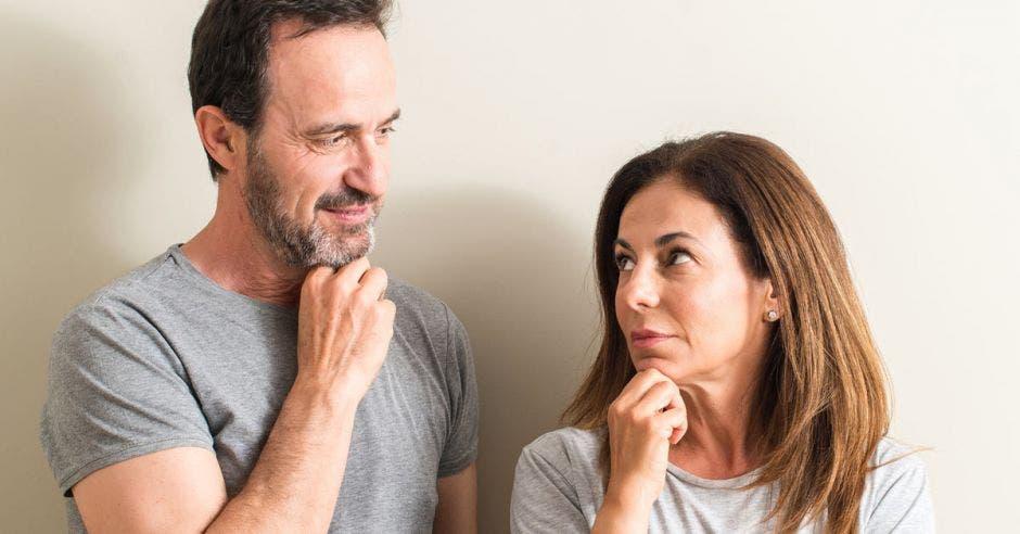 un hombre y una mujer adultos con la mano en la barbilla y expresión pensativa