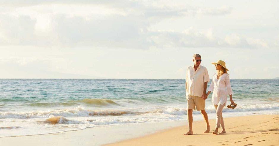 Una pareja de adultos mayores camina descalza por la arena