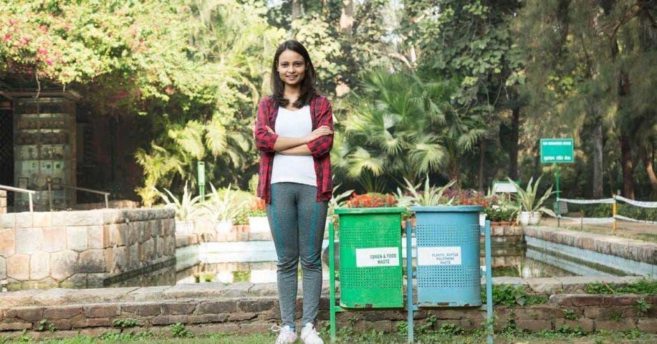 Una mujer posa junto a dos potes reciclaje