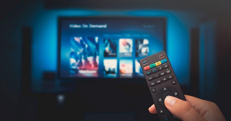 Mano cambiando opciones de programas en la televisión con el control