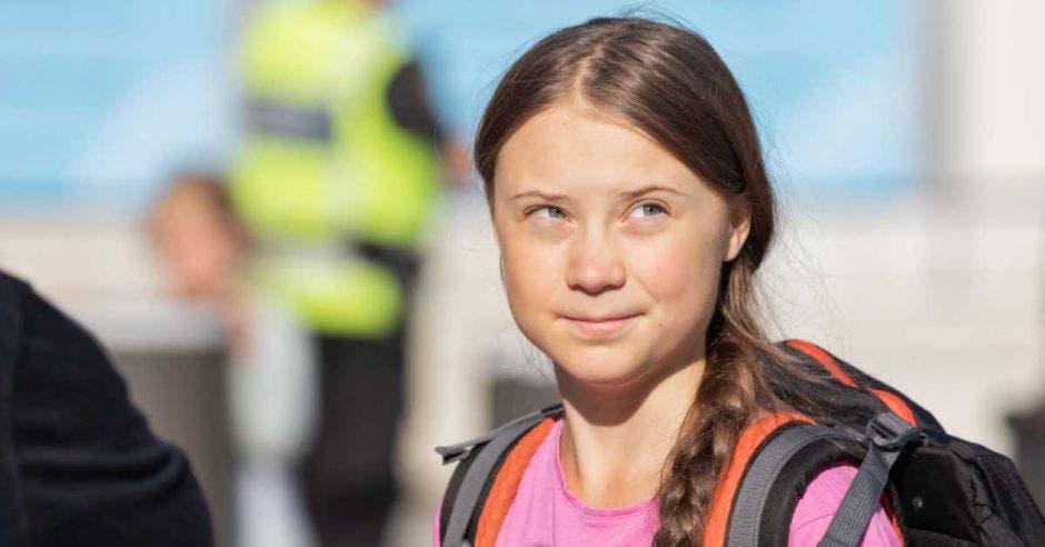 Greta Thunberg con una blusa rosada y un salveque color anaranjado