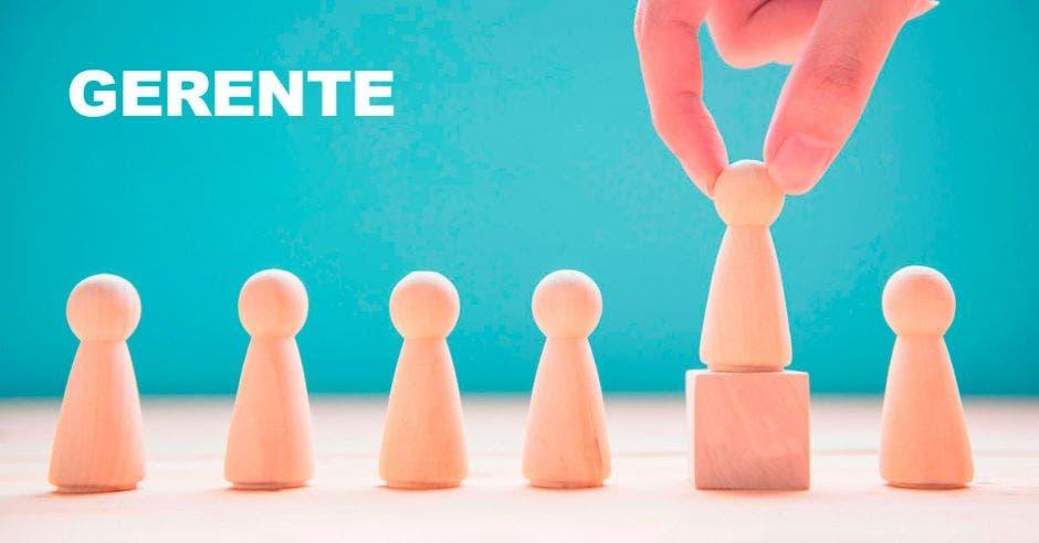 piezas de ajedrez de madera, una levantada por una mano, palabra gerente de fondo.
