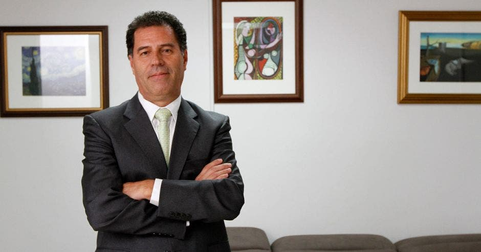 German Morales posa en una oficina con cuadros de fondo