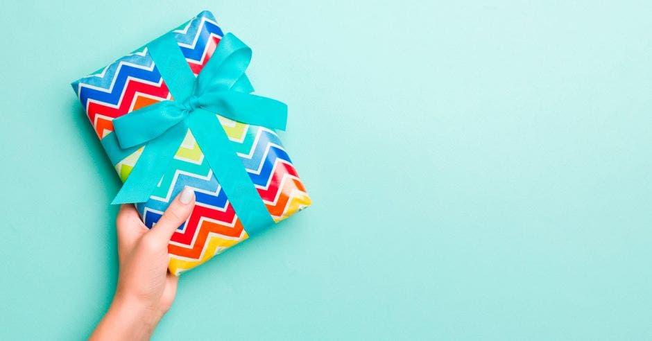 Persona sostiene en su mano un regalo envuelto en papel y un lazo