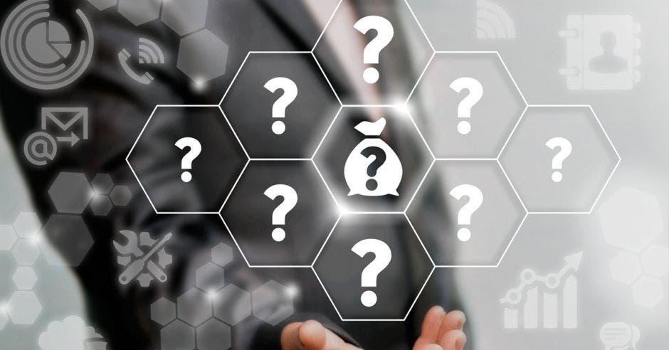 signos de pregunta en blanco rodean a una bolsa de dinero. De fondo una persona en traje entero señala los signos de pregunta.
