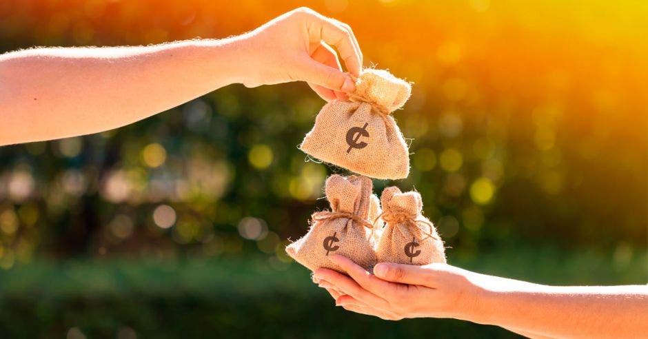 Una mano dando bolsas de dinero a otra mano