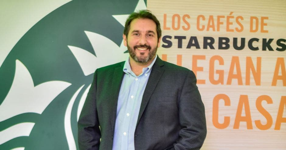 Carlos Quevedo posa con letrero de Starbucks atrás