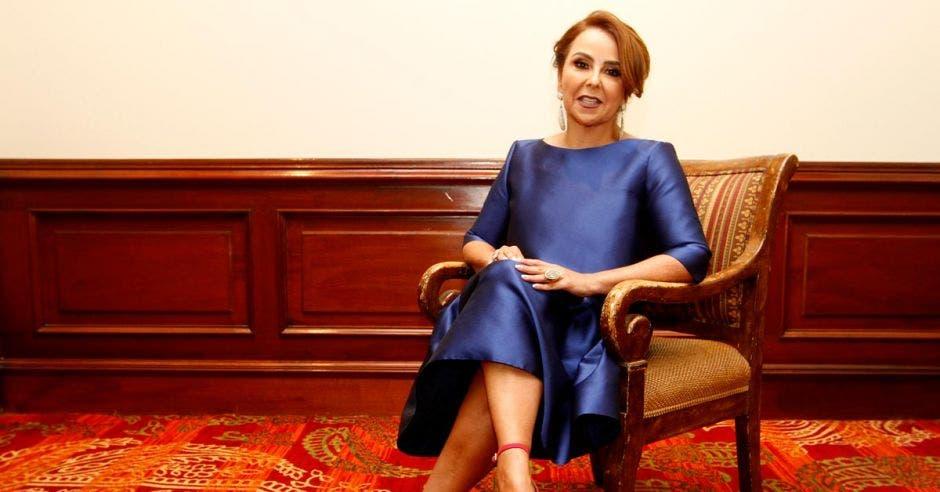 Laura Bonilla, presidenta de Cadexco, sentada en una silla mientras luce un vestido morado