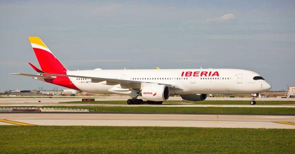 Un Airbus A350 color blanco con rojo en una pista de aterrizaje